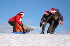 Two men pull two women on sled Royalty Free Stock Photography