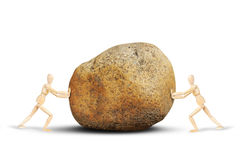 Two men push a huge stone to each other Royalty Free Stock Images