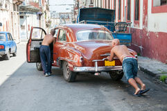 Two men pushing the car in the street Stock Images