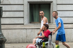Two men pushing a wheelchair Royalty Free Stock Photo