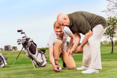 Two men putting ball on tee at course Royalty Free Stock Photos