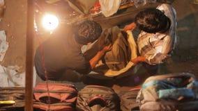 Two men putting material in a big sack bag at flea market, Mumbai, India
