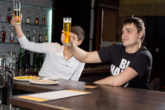 Two men raising their beer glasses in a toast. Two young men sitting at the bar counter in a club raising their beer glasses high in the air in a toast as they Stock Photography