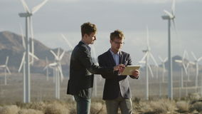 Two men reaching an agreement near the windmills stock video footage