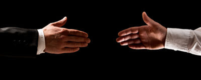 Two men reaching out to shake hands Stock Photos