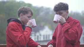 Two men in red jackets cheers with coffe cups and smile Friends spend time outdoors together Male friendship. Two men in red jackets cheers with coffee cups and stock footage