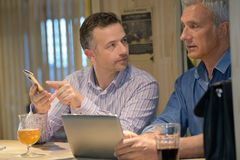 Two men relaxing with beers and touch pad royalty free stock photography