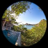 Peaceful tropical getaway. Two men relaxing in a peaceful pool overlooking the pacific ocean in Nicaragua shot with a fisheye lens creating a circl=ular effect Stock Photo
