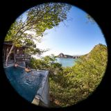 Peaceful tropical getaway. Two men relaxing in a peaceful pool overlooking the pacific ocean in Nicaragua shot with a fisheye lens creating a circl=ular effect Stock Photography