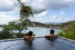 Peaceful tropical getaway. Two men relaxing in a peaceful pool overlooking the pacific ocean in Nicaragua Stock Photo