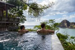 Peaceful tropical getaway. Two men relaxing in a peaceful pool overlooking the pacific ocean in Nicaragua Stock Photography