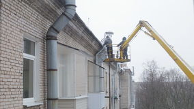 Two men removing icicles. Two men in autotower removing snow and icicles from the roof stock video