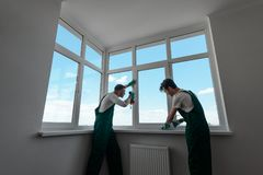 Two men are repairing home. Two men are repairing customer`s home. Fixing a window handle and applying silicone sealant. Local handyman company employees stock image