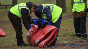 Two men in rescue uniform unfolded orange tent in forest. Emercom camping stock video