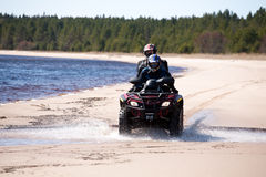Two men riding all-terrain vehicle. Two men riding small all-terrain vehicle on sandy coast of forest lake, front view Royalty Free Stock Photo