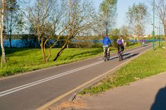 Two men riding bicycle. In a park near the grass. Healthy lifestyle concept stock images