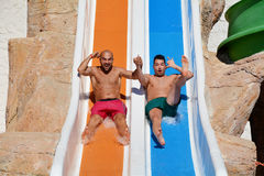 Two men riding down a water slide-friends  enjoying a water tube ride Stock Image