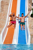 Two men riding down a water slide-friends  enjoying a water tube ride Royalty Free Stock Image
