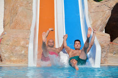 Two men riding down a water slide-friends  enjoying a water tube ride Royalty Free Stock Photos