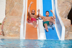 Two men riding down a water slide-friends  enjoying a water tube ride Stock Photography