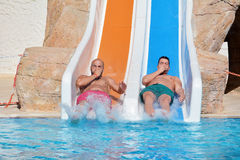 Two men riding down a water slide-friends  enjoying a water tube ride Royalty Free Stock Photography