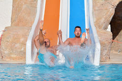 Two men riding down a water slide-friends  enjoying a water tube ride Stock Photos