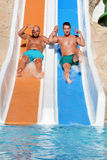 Two men riding down a water slide-friends  enjoying a water tube ride Stock Photo