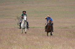 Two men riding horses at speed Royalty Free Stock Photos
