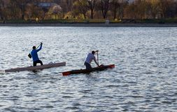Two men are riding a kayak royalty free stock photos