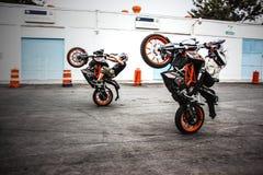 Two Men Riding Orange-and-black Sports Bikes While Doing Exhibition Royalty Free Stock Photo