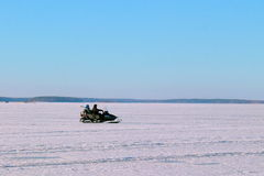 Two men riding on a snowmobile winter Royalty Free Stock Images
