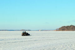Two men riding on a snowmobile winter Royalty Free Stock Photography