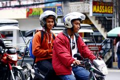 Two men riding in tandem on a motorcycle in Antipolo City. Royalty Free Stock Photos