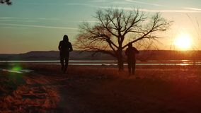 Two men on the road at sunset standing alone tree silhouette. Athletic young man running in the nature in Pine the. Two men on the road at sunset standing alone stock footage
