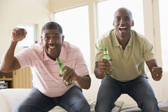 Two men in room with beer bottles cheering Royalty Free Stock Images