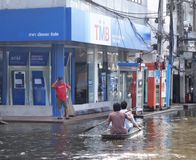 Two men in a rowing boat pass by a TMB bank in a flooded street in Rangsit, Thailand, in October 2011.  Stock Photography