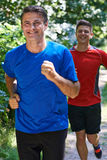 Two Men Running In Countryside Together Stock Photos