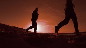 Two men running along the beach on the sand evening sun sunset , the runner. Two men running along the beach on the sand evening sun sunset , runner stock footage