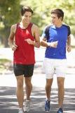 Two Men Running Through Park Stock Image