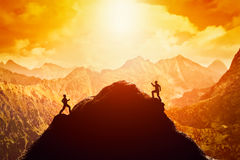 Two men running race to the top of the mountain. Competition, rivals, challenge Royalty Free Stock Image