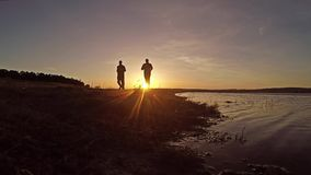 Two men running at sunset along the river bank beautiful the sport stock footage