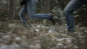 Two men running through the woods. Slow motion stock footage