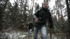 Two men running through the woods. Slow motion.  stock footage