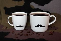 Two men`s cups with mustaches on a background of coffee and khaki. Military stock photography