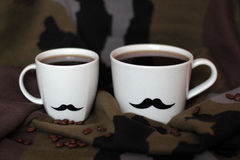 Two men`s cups with mustaches on a background of military. Two men`s cups with mustaches on a background of coffee and khaki stock photo