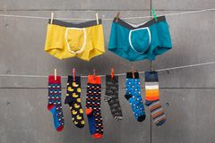 Two men`s shorts and many colored socks are hanging on the ropes, as if drying after washing, concept, on a gray background. Two men`s shorts and many colored stock photo