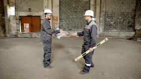 Two men in safety hardhats having meeting on building site and shaking hands to each other. Builder walking to foreman stock footage