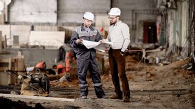 Two men in safety helmets standing in construction area and looking at scheme of future building. Foreman pointing to. Two men in white safety helmets are stock video