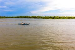 Two Men Sailing a Boat Up the River Along a Flooded Forest Line. Under a Clear Blue Sky stock images