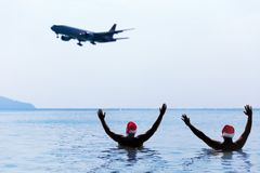 Two men in Santa Claus red hat greet salute airplane in morning. Hangover after Christmas holiday party Stock Photography